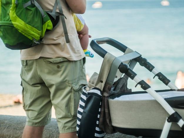 屋外家族の概念を歩くストーラーの近くに立って腕の中で赤ちゃんの子供を持つお父さんの背面図