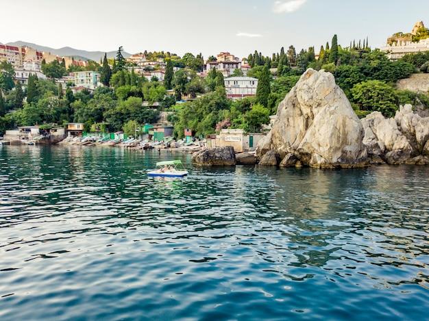 Небольшой туристический катамаран, проходящий мимо скалистого утеса на берегу моря