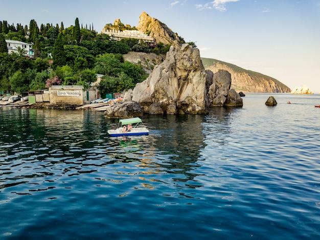 海の上の岩の崖の海岸を通過する観光の小さなカタマラン