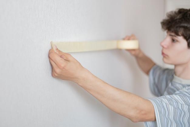 Мужской работник, используя малярный скотч, чтобы покрасить стену