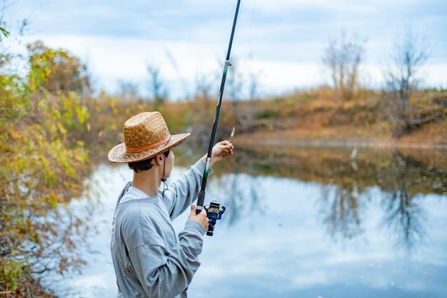 湖のそばに座って帽子の若い男と設定をセットアップし、釣り竿を調整