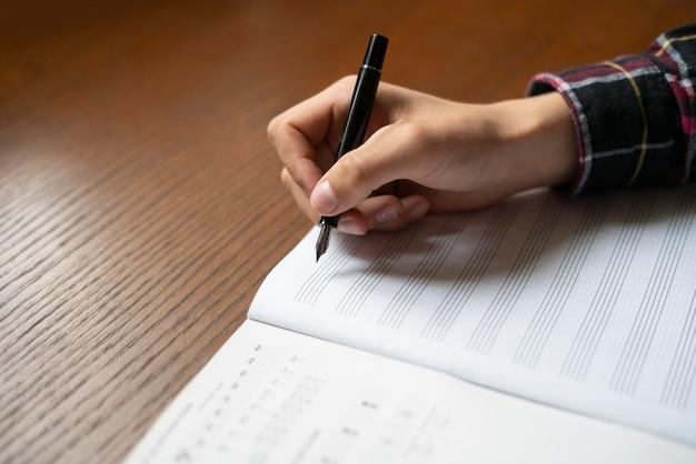 学生の手を閉じる学校でクラスの音符を書き留めます