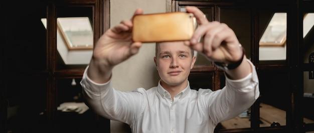 Молодой счастливый офисный работник делает селфи на рабочем месте с смартфон