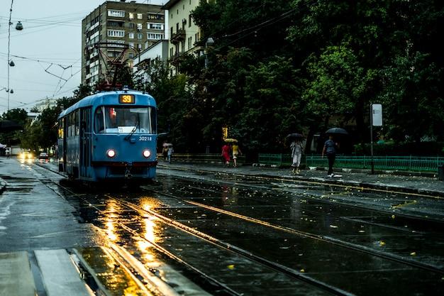 Старинный городской трамвай движется по улице во время дождя вечером