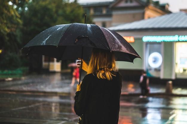 市内の雨の中に歩いている女性の背面図