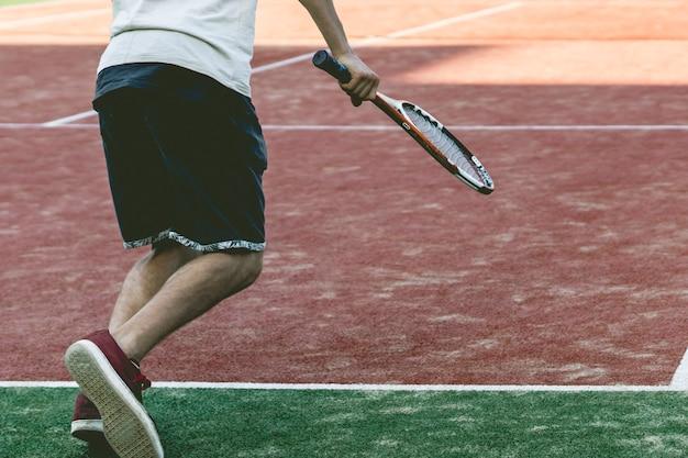 夏のキャンプの練習に若いスポーツの男性のテニス選手