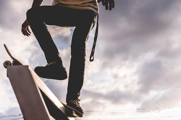 空に対するトリックの前にスケートボードの上に立ってライダー