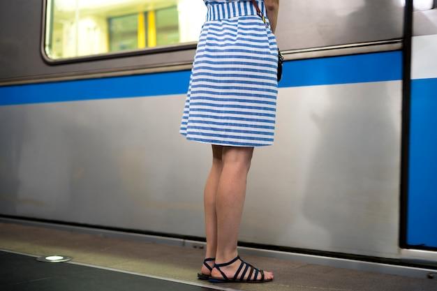 Молодая женщина в платье стоит на пероне рядом с проходящим поездом
