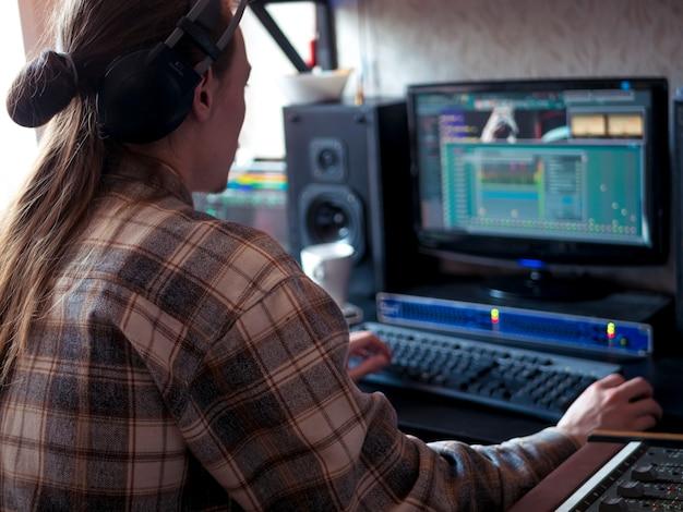 プロの音楽機器と自宅のスタジオで座っている男の人