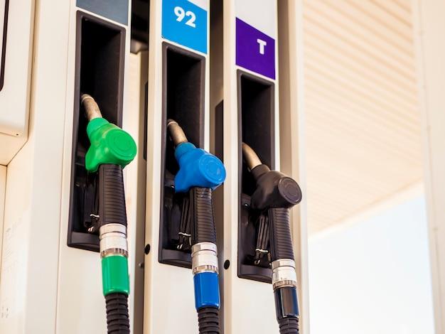 ガソリンスタンドはガスでカラフルな燃料ポンプノズルを閉じる