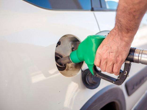 Крупным планом рука человека, заполняя белый автомобиль топливом