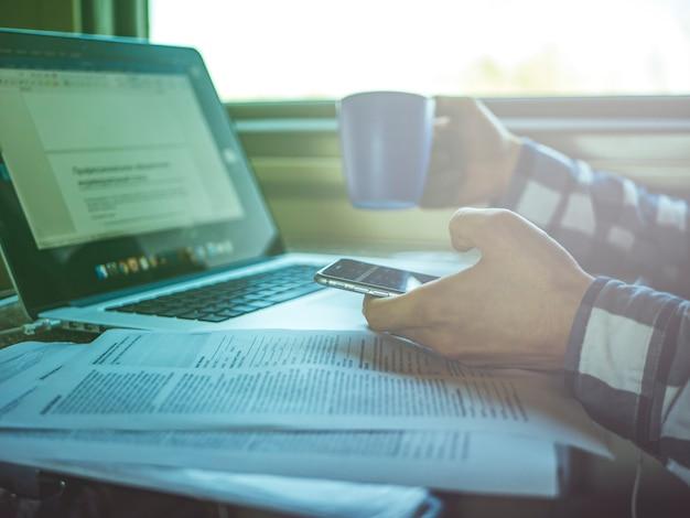 窓の近くの電車の中でノートパソコンと紙を扱うフリーランサー