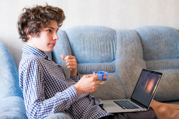 Молодой усмехаясь подросток с длинными волосами изучая дома используя компьтер-книжку сидя на софе