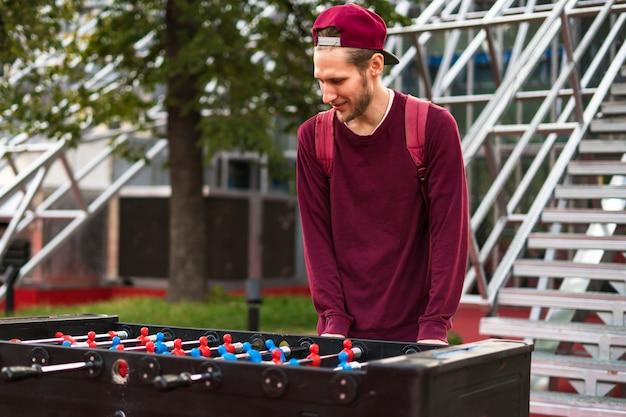 公共の公園でフーズボールをしているカジュアルな服装の若い男。テーブルゲームのコンセプト