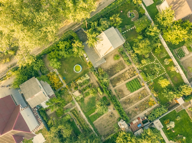 夏の田舎のコテージと庭の空中ドローンショット。