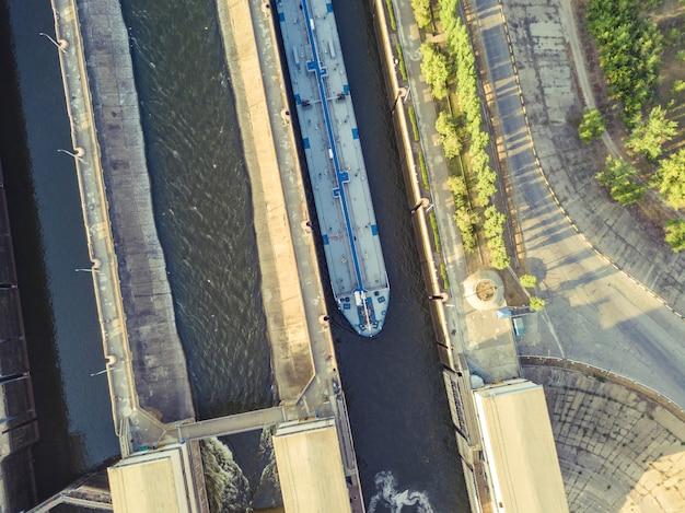 バージ貨物船の川のゲートウェイ構造の空中ドローンショット。