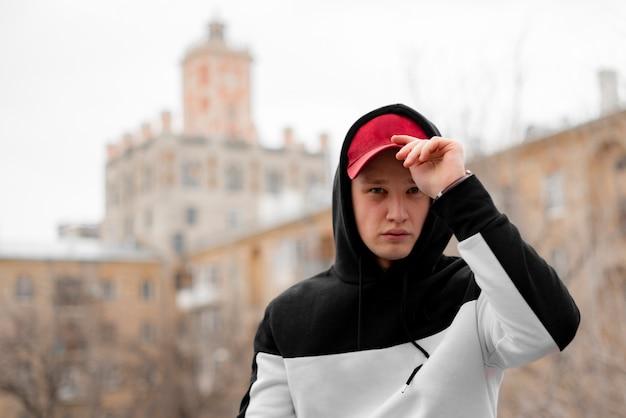 Стильный мужчина в капюшоне в городском городе, концепция современной модной одежды