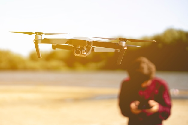 Заделывают летающий дрон в воздухе с человеком с контроллером на заднем плане.
