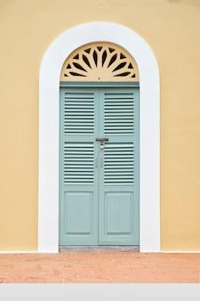 ビンテージグリーンウィンドウと黄色の壁のドア