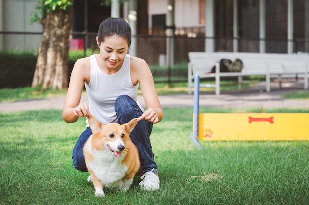 Азиатская женщина с валлийской собакой корги пембрук