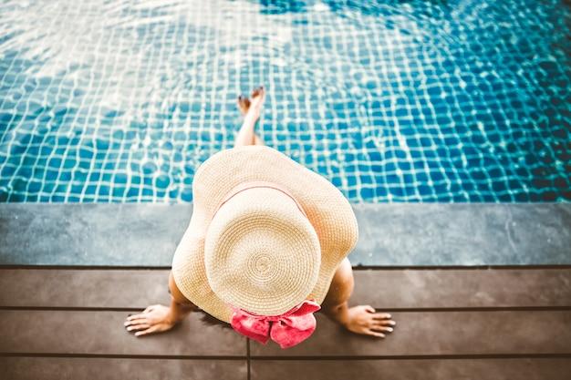 アジアの女性はプールのプールでリラックス