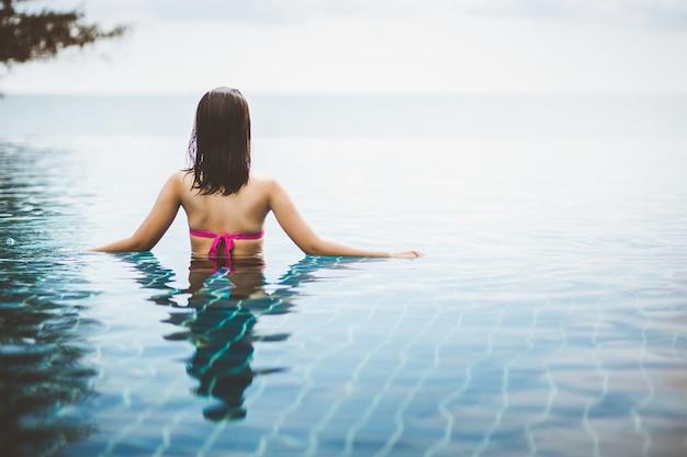 アジアの女性はビーチのプールでリラックス