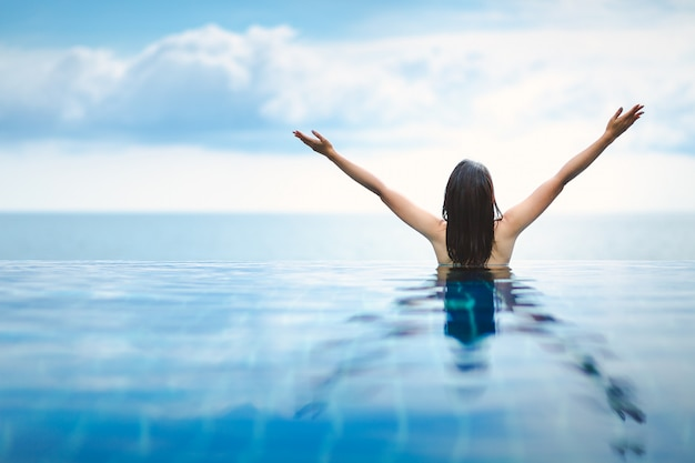 アジアの女性はビーチでプールでリラックスします。