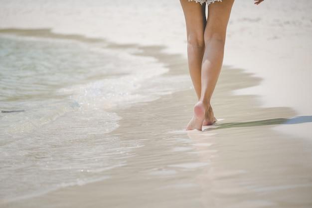 Путешествие женщины ногой на пляже