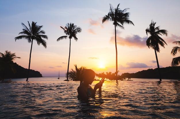 Азиатская женщина расслабиться в бассейне на пляже
