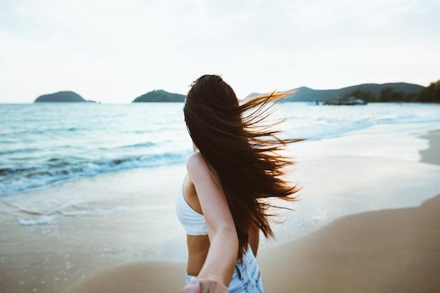 日没のビーチで手を繋いでいるカップル