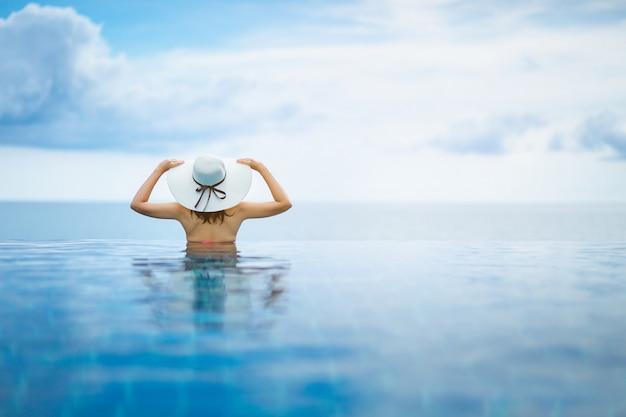 アジアの女性はビーチのプールでリラックスします。