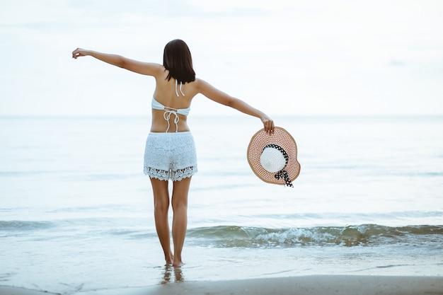 日没のビーチを歩いて旅行女性