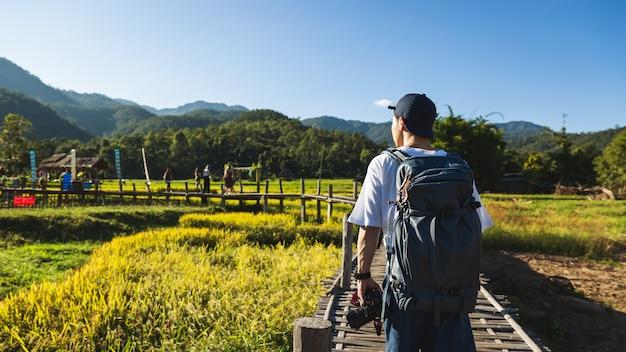 Человек путешественника гуляя на мост в полях природы