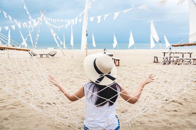 幸せな女はビーチでハンモックでリラックスします。