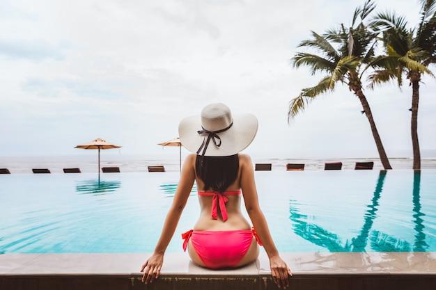 Азиатская женщина путешественник расслабиться в бассейне на пляже