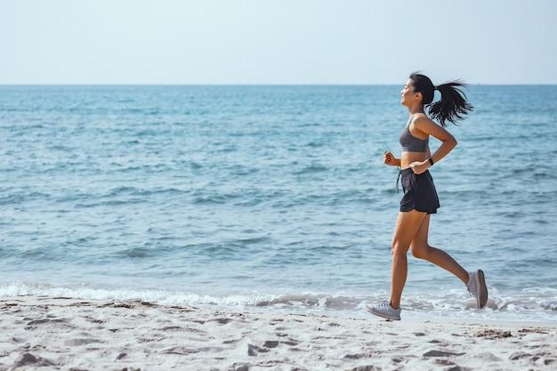 幸せなアジアランナー女性がビーチで一人で走る