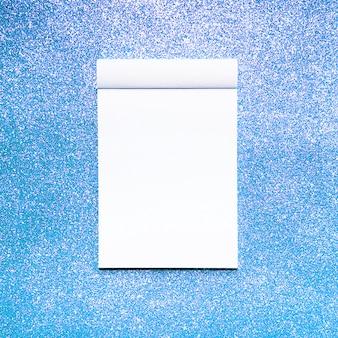 青いキラキラの背景を持つモックアップノート