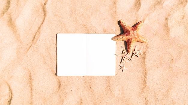 空白のノートブックと砂の背景にヒトデ