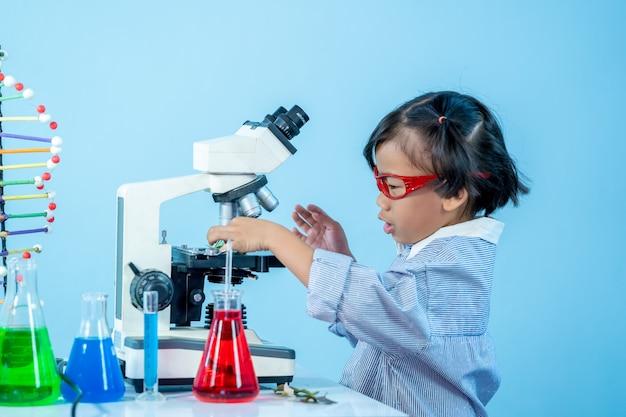 Маленькая девочка проводит научные эксперименты, маленький ученый.