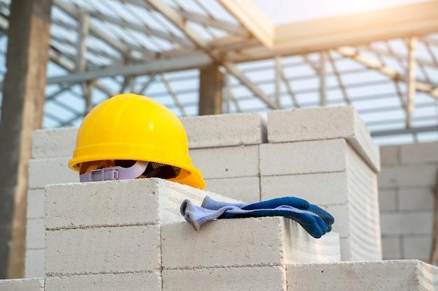 Желтая каска дальше на концепциях конструкции строительной площадки, каски и перчатки.
