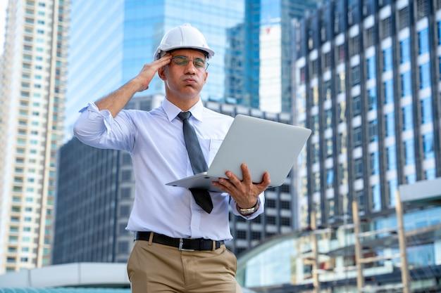 Шлем безопасности человека инженера нося над городом страдая от головной боли отчаянной и усиленной потому что боль и мигрень, депрессия от концепции трудной работы.