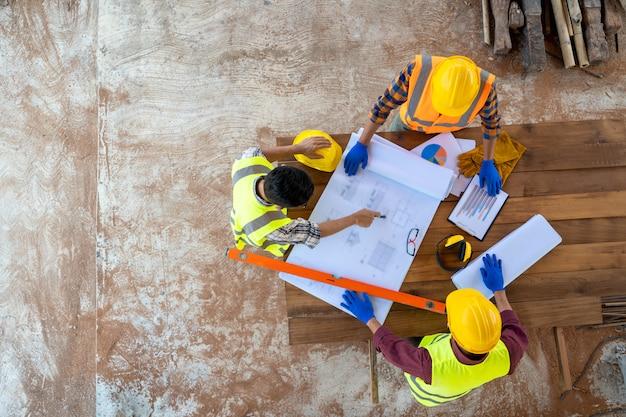 Взгляд высокого угла инженера и архитектора обсуждая план здания на строительной площадке, группе в составе строители имея беседу о плане здания.