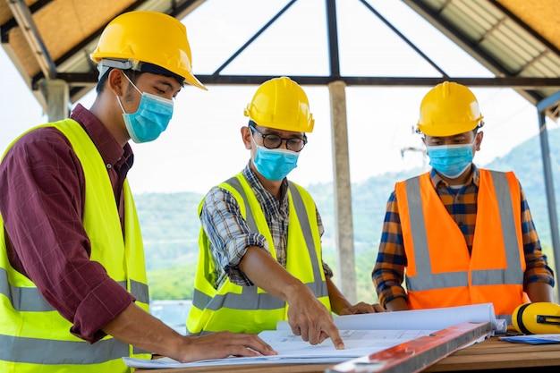 Команда инженеров и строителей, носящих защитные маски для предотвращения пыли и ковидных заболеваний во время осмотра на строительной площадке, превратилась в глобальную чрезвычайную ситуацию.