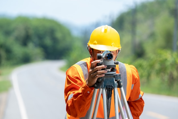 建設現場の測量技師は道路でセオドライトマークを使用します。建設コンセプト。