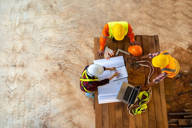 Команда инженера и архитекторов работая, встречая, обсуждающ, конструирующ, планируя, измеряя план здания планирует на строительной площадке, взгляд сверху, концепция конструкции.