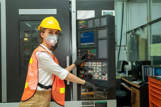 Работник женского техника работая и проверяя машину в крупной промышленной фабрике