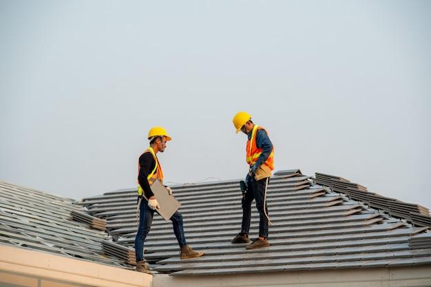 Кровельщик использует пневматический или пневматический гвоздевой пистолет и укладывает бетонную черепицу на новую крышу.