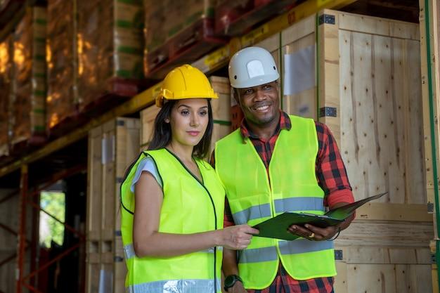 アフリカ系アメリカ人の労働者が倉庫でクリップボードを操作します。