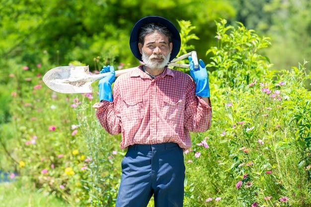 裏庭の庭でシャベルを扱う老人。