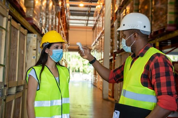 倉庫作業員、体温チェック、伝染病予防のウイルス防止コンセプト、医療用体温計。